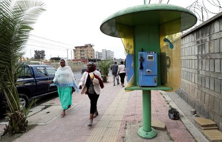 FILE PHOTO: Pedestrians walk by a telephone booth in Addis Ababa