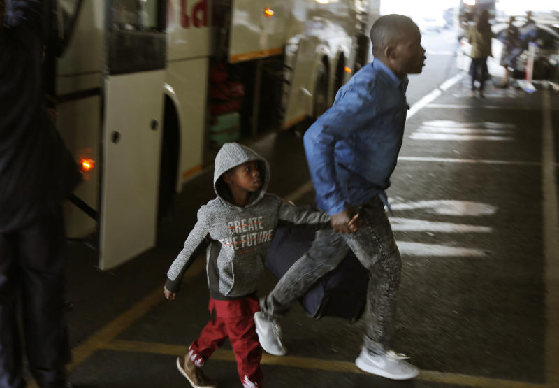 Nigerians exit a bus at the O.R. Tambo International Airport in Johannesburg, South Africa, Wednesday, Sept. 11, 2019. A group of Nigerians boarded a free flight from Johannesburg to Lagos on Wednesday, following a week of violence targeting foreigners in South Africa that has stoked tensions between Africa's two largest economies. It was not immediately clear how many people were on board the flight, operated by the private Nigerian airline Air Peace, but Nigeria's government said it estimated 313 people would board.(AP Photo/Denis Farrell)