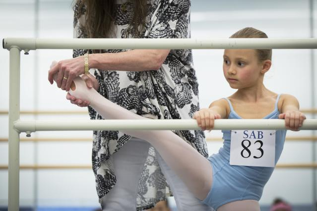 A faculty member checks the limberness of a girl during an audition for the School of American Ballet in New York April 25, 2014. The school is holding auditions for over 600 beginner ballet students, who will be selected to fill the 120 spots available to study the dance on campus. REUTERS/Lucas Jackson (UNITED STATES - Tags: SOCIETY EDUCATION)
