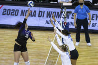 Washington outside hitter Madi Endsley (18) spikes the ball against Kentucky's Elise Goetzinger (11) and Madi Skinner (2) during the first set of a semifinal in the NCAA women's volleyball championships Thursday, April 22, 2021, in Omaha, Neb. (AP Photo/John Peterson)
