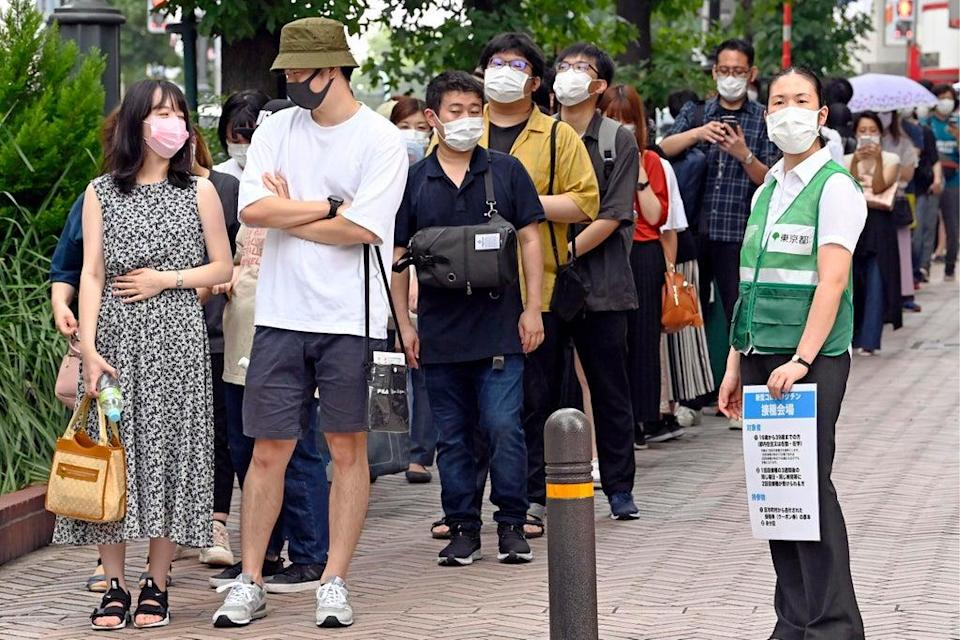 People wait in line to get lottery tickets for the coronavirus vaccine at the Shibuya district in Tokyo Saturday (AP)