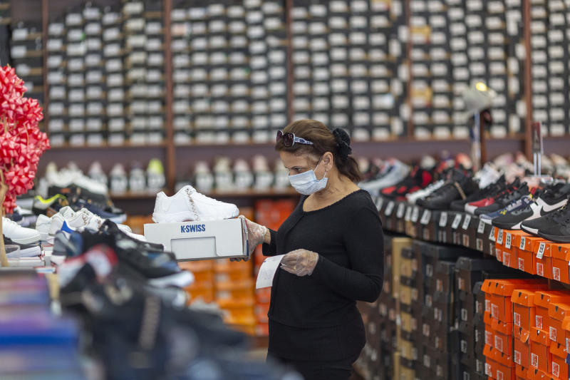 GLENDALE, CA - MAY 27: An employee stocks merchandise at a Shoe City store as Los Angeles County retail businesses reopen while the COVID-19 pandemic continues on May 27, 2020 in Glendale, Californias latest guidelines and allow the resumption of in-store shopping at low-risk retail stores, faith-based services, drive-in theaters and other recreational activities with reduced capacities and social distancing restrictions, starting today. Not reopening yet are personal services locations like hair salons and dining in at restaurants. (Photo by David McNew/Getty Images)