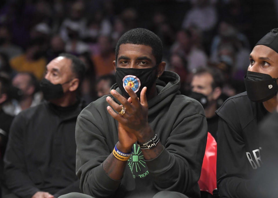 Kyrie Irving watches from the bench during the Brooklyn Nets' preseason opener against the Lakers in Los Angeles. (Kevork Djansezian/Getty Images)