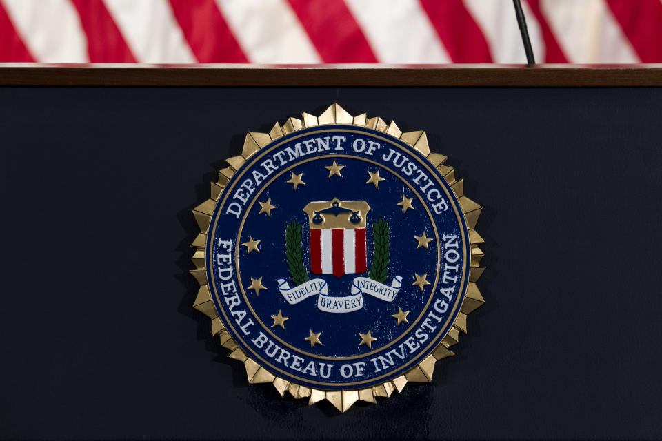 FILE - In this June 14, 2018, file photo, the FBI seal is seen before a news conference at FBI headquarters in Washington. The FBI says it is getting serious about sexual harassment in its ranks, starting a 24/7 tip line, doing more to help accusers and taking a tougher stand against agents found to have committed misconduct. (AP Photo/Jose Luis Magana, File)