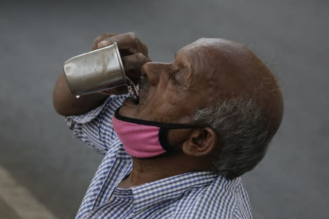 An Indian man selling earthen pots beneath a bridge drinks water in Ahmedabad, India (Ajit Solanki/AP)