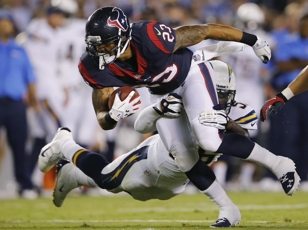 Houston Texans running back Arian Foster (23) is tackled by San Diego Chargers inside linebacker Donald Butler during their Monday Night NFL football game in San Diego, California September 9, 2013.REUTERS/Mike Blake (UNITED STATES - Tags: SPORT FOOTBALL)