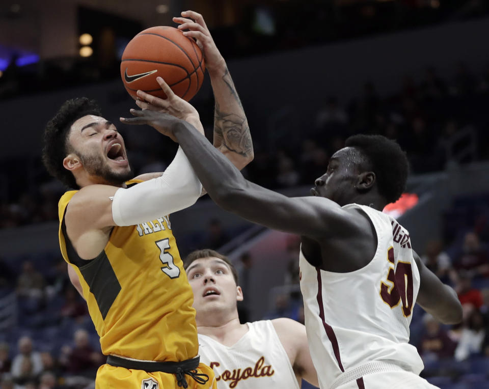 Valparaiso's Markus Golder (5) is fouled on his way to the basket by Loyola of Chicago's Aher Uguak (30) as Loyola's Cameron Krutwig watches during the second half of an NCAA college basketball game in the quarterfinal round of the Missouri Valley Conference tournament, Friday, March 8, 2019, in St. Louis. Loyola won 67-54. (AP Photo/Jeff Roberson)