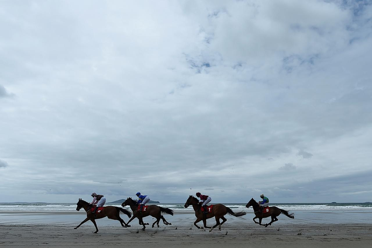Runners and riders compete during a race meet on the beach in Carrowniskey, Ireland June 25, 2017. REUTERS/Clodagh Kilcoyne     TPX IMAGES OF THE DAY
