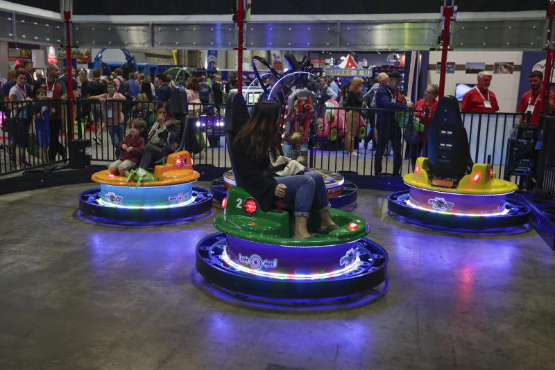 Bumper cars that spin and display flashing lights were part of the items on display at the International Association of Amusement Parks and Attractions convention Tuesday, Nov. 19, 2019, in Orlando, Fla. (AP Photo/John Raoux)