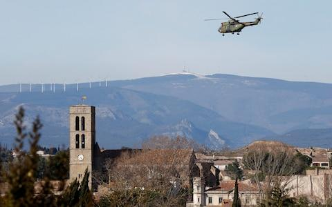 A military helicopter flies over the village of Trebes - Credit: JEAN-PAUL PELISSIER/Reuters