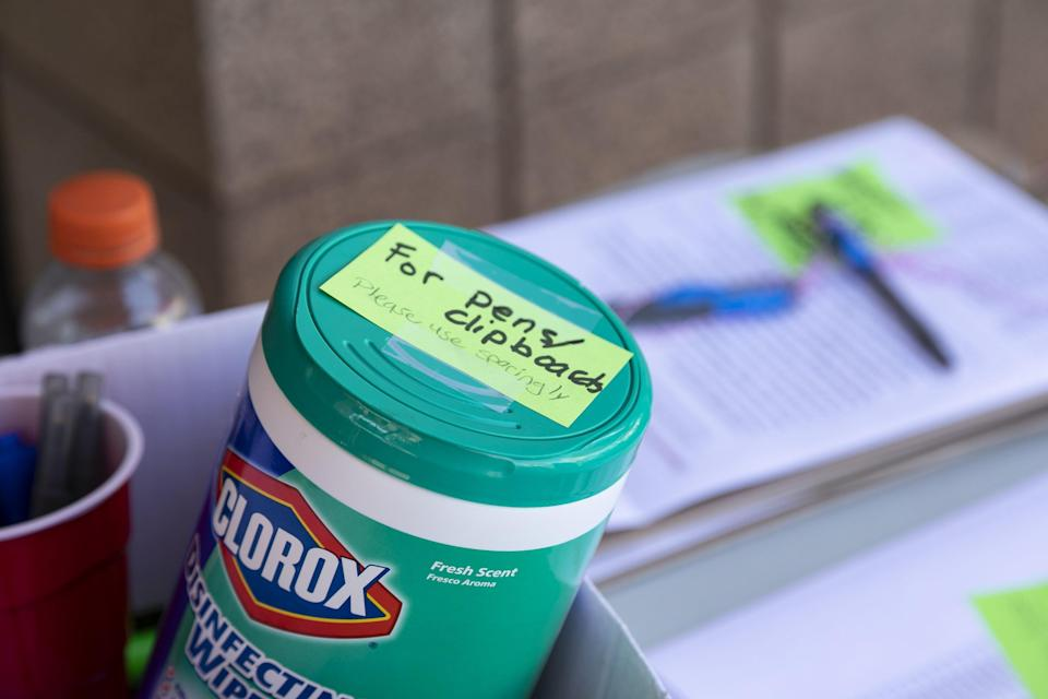 Clorox disinfectant wipes sit beside face masks, gloves, hand sanitizer and other supplies on table while new residents move into Arizona State University Downtown Phoenix Campus residence hall Taylor Place in Phoenix on Aug. 7, 2020.