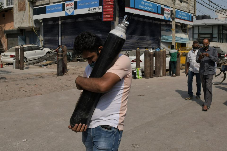 FILE - In this May 3, 2021, file photo, a man walks carrying a refilled cylinder as family members of COVID-19 patients wait in queue to refill their oxygen cylinders at Mayapuri area in New Delhi, India. COVID-19 infections and deaths are mounting with alarming speed in India with no end in sight to the crisis. People are dying because of shortages of bottled oxygen and hospital beds or because they couldn't get a COVID-19 test. (AP Photo/Ishant Chauhan, File)