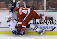 Detroit Red Wings right wing Luke Glendening (41) checks Vancouver Canucks defenseman Kevin Bieksa (3) during the second period of an NHL hockey game in Detroit, Sunday, Nov. 30, 2014. (AP Photo/Carlos Osorio)