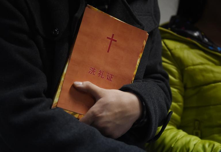A man holds a certificate of baptism after he was baptised during a Christmas Eve service held at an apartment in Beijing by members of an underground church, on December 24, 2014