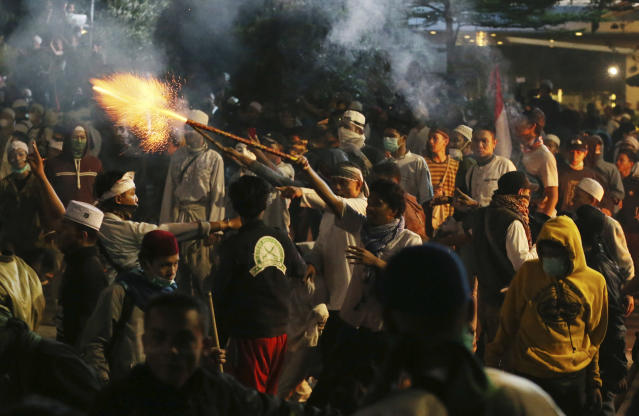 Supporters of the losing presidential candidate use fireworks toward police Wednesday, May 22, 2019. in Jakarta, Indonesia. Indonesian President Joko Widodo said authorities have the volatile situation in the country's capital under control after a number of people died Wednesday in riots by supporters of his losing rival in last month's presidential election. (AP Photo/Achmad Ibrahim)