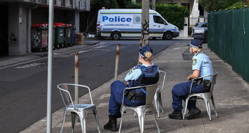 NSW police officers wearing face masks guard the entrance of the Urban Newtown hotel. Australian travellers were quarantined inside.
