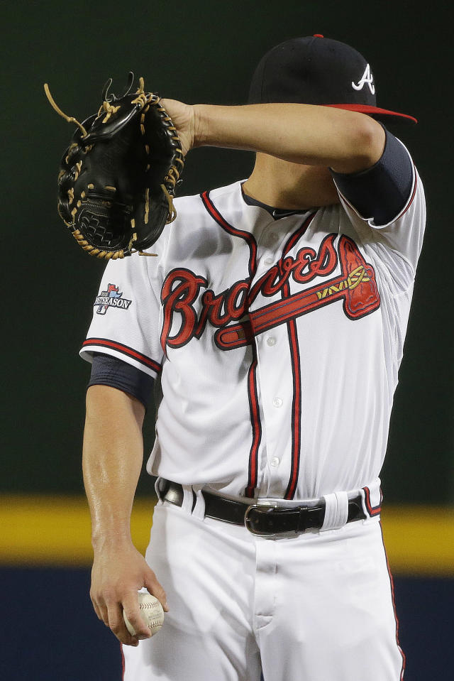 Atlanta Braves starting pitcher Kris Medlen wipes his face in the third inning of Game 1 of the National League Divisional Series against the Los Angeles Dodgers, Thursday, Oct. 3, 2013, in Atlanta. (AP Photo/David Goldman)