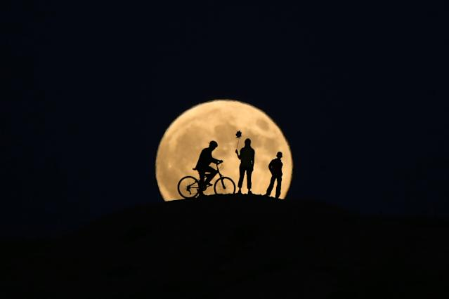 "<p>The full moon rises behind silhouettes of people prior to the totally phase of Century's longest ""Blood Moon"" eclipse in Van, Turkey on July 27, 2018. (Photo: Ozkan Bilgin/Anadolu Agency/Getty Images) </p>"