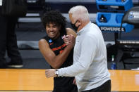 Oregon State guard Ethan Thompson (5) and head coach Wayne Tinkle celebrate beating Oklahoma State 80-70 after a men's college basketball game in the second round of the NCAA tournament at Hinkle Fieldhouse in Indianapolis, Monday, March 22, 2021. (AP Photo/Paul Sancya)