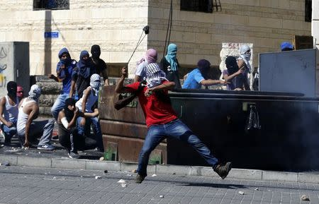 Palestinian hurls a stone towards Israeli police during clashes in Shuafat
