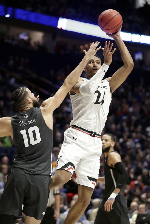 Cincinnati forward Kyle Washington (24) drives to the basket over Nevada forward Caleb Martin (10), during the second half of a second-round game in the NCAA college basketball tournament in Nashville, Tenn., Sunday, March 18, 2018. (AP Photo/Mark Humphrey)