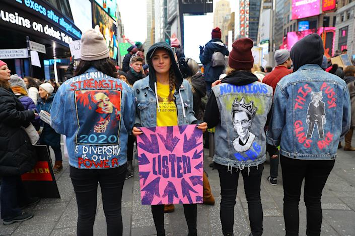 Several young women show off their politically motivated denim jackets in Time Square after participating in the Women's March in New York City on Jan. 19, 2019 in New York City. (Photo: Gordon Donovan/Yahoo News)