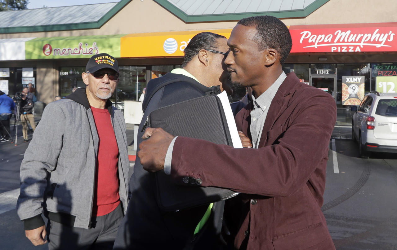 Byron Ragland, right, is embraced by Eddie Rye Jr. before Ragland addressed media members in front of the frozen-yogurt shop behind them Tuesday, Nov. 20, 2018, in Kirkland, Wash. The police department there has apologized for an incident in which officers helped the owner of the Menchie's shop expel Ragland, an African-American man, from the business because employees said they felt uncomfortable. The Seattle Times reported that the shop's owner called police on Nov. 7 about Ragland, who works as a court-appointed special advocate, who was in the shop supervising a court-sanctioned outing between a mother and her son. (AP Photo/Elaine Thompson)