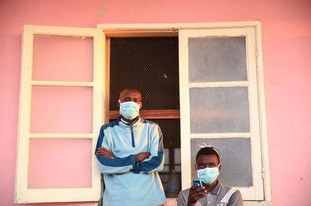 Tuberculosis patients, wearing masks to stop the spread of the disease, stand outside their ward at Chiulo Hospital, Cunene province, Angola February 22, 2018.  REUTERS/Stephen Eisenhammer