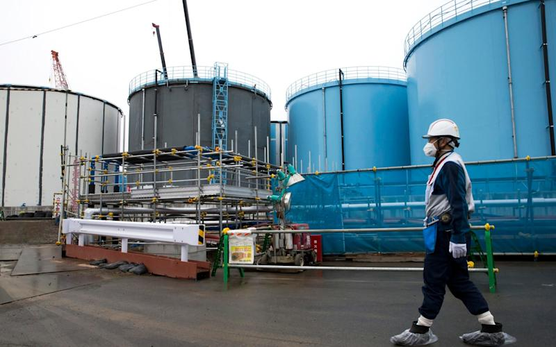 A Tepco employee walks past storage tanks containing contaminated water at the crippled Fukushima Da-ichi nuclear power plant - Pool Bloomberg