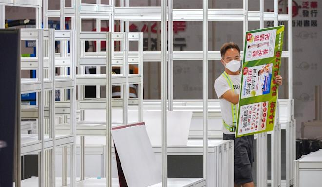 A worker removes booths set up for the 2020 Hong Kong Book Fair in July after the annual fair was postponed due to a spike in locally transmitted coronavirus cases. Photo: Sam Tsang