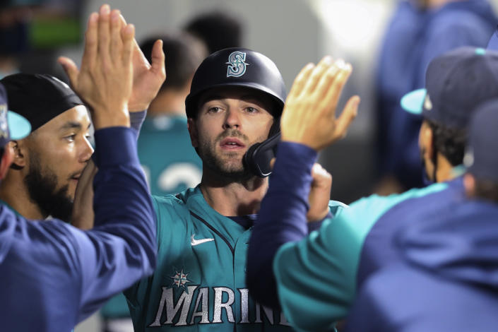 Seattle Mariners' Mitch Haniger celebrates in the dugout after scoring on a Kyle Seager double during the sixth inning of the team's baseball game against the Houston Astros on Friday, April 16, 2021, in Seattle. (AP Photo/Jason Redmond)
