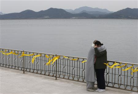 A Buddhist nun comforts the crying family member of a missing passenger onboard the capsized Sewol ferry at a port in Jindo April 26, 2014. REUTERS/Kim Kyung-Hoon