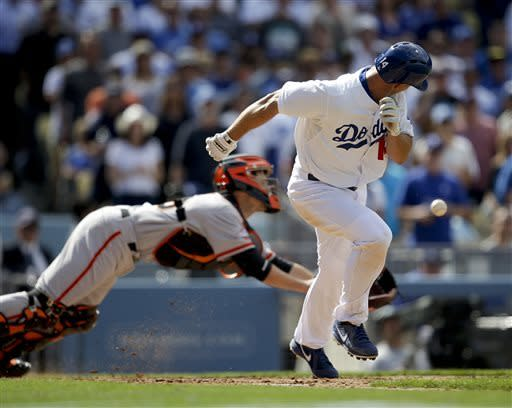 Los Angeles Dodgers' Mark Ellis watches San Francisco Giants catcher Buster Posey go after his bunt during the eighth inning of a season opening baseball game in Los Angeles, Monday, April 1, 2013. (AP Photo/Jae C. Hong)