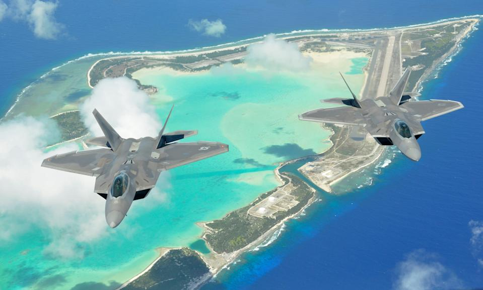 Two F-22 Raptors fly over Wake Island as part of a rapid deployment June 21, 2013.