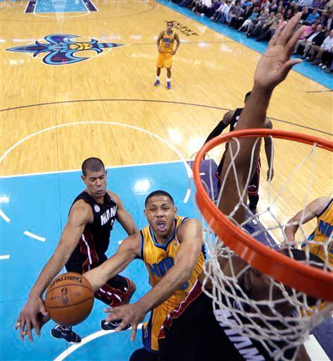 New Orleans Hornets guard Eric Gordon goes to the basket against Miami Heat center Chris Bosh, hand in foreground, during the first half of an NBA basketball game in New Orleans, Friday, March 29, 2013. (AP Photo/Gerald Herbert)