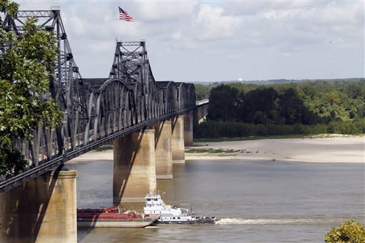 A towboad and its barges pass under the old Mississippi River bridge at Vicksburg, Miss., Thursday, July 26. 2012. in a switch of extremes, the river has dropped to very low levels this summer unlike last year when the river was flooding much of the Delta due to record high levels. The drop in water level now exposes the river bottom, forcing river traffic to a trickle as barges are forced to lessen their loads to keep from getting stuck on sandbars. (AP Photo/Rogelio V. Solis)