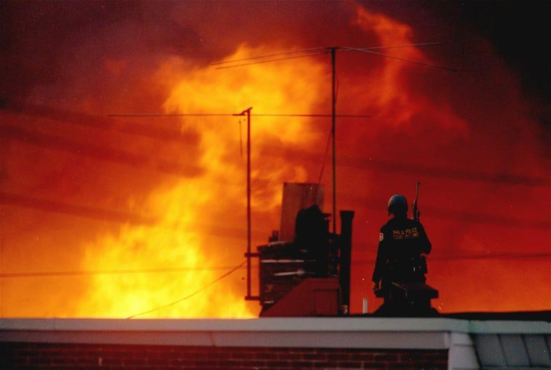 In this May, 1985 file photo, a Philadelphia policeman is seen on a rooftop as flames rise from a row of burning homes beyond, in Philadelphia. The fire started when police dropped a bomb onto the house of the militant group MOVE, on May 13, 1985 and fire spread throughout the area.