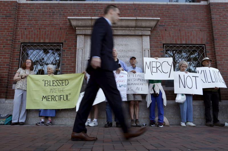 FILE PHOTO: A pedestrian walks past death penalty protesters before the formal sentencing of convicted Boston Marathon bomber Dzhokhar Tsarnaev at the federal courthouse in Boston