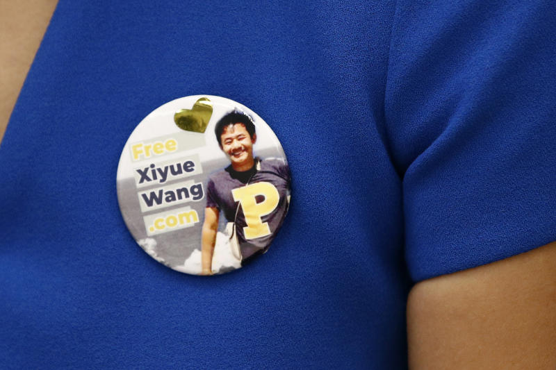 Hua Qu, the wife of Xiyue Wang, a Princeton University graduate student being held at an Iranian prison, wears a button bearing a picture of her husband as she speaks at a news conference to mark the third anniversary of his imprisonment, Thursday, Aug. 8, 2019, at the National Press Club in Washington. (AP Photo/Patrick Semansky)