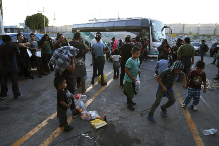 Migrants wait outside at an immigration center on the International Bridge 1, in Nuevo Laredo, Mexico, Tuesday, July 16, 2019. A U.S. policy to make asylum seekers wait in Mexico while their cases wind through clogged U.S. immigration courts has also expanded to the violent city of Nuevo Laredo. The group was returned from the U.S. after being detained and will be bused back to the Mexican city of Monterrey. (AP Photo/Marco Ugarte)