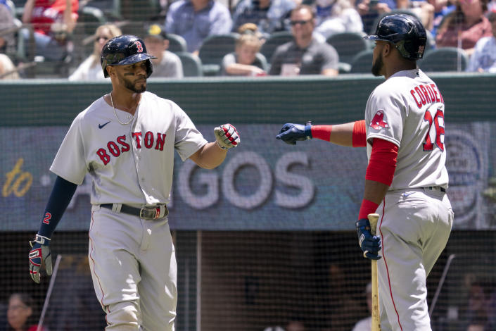Boston Red Sox's Xander Bogaerts, left, is congratulated by Franchy Cordero (16) after scoring on a groundout by Hunter Renfroe during the first inning of a baseball game against the Texas Rangers Sunday, May 2, 2021, in Arlington, Texas. (AP Photo/Jeffrey McWhorter)