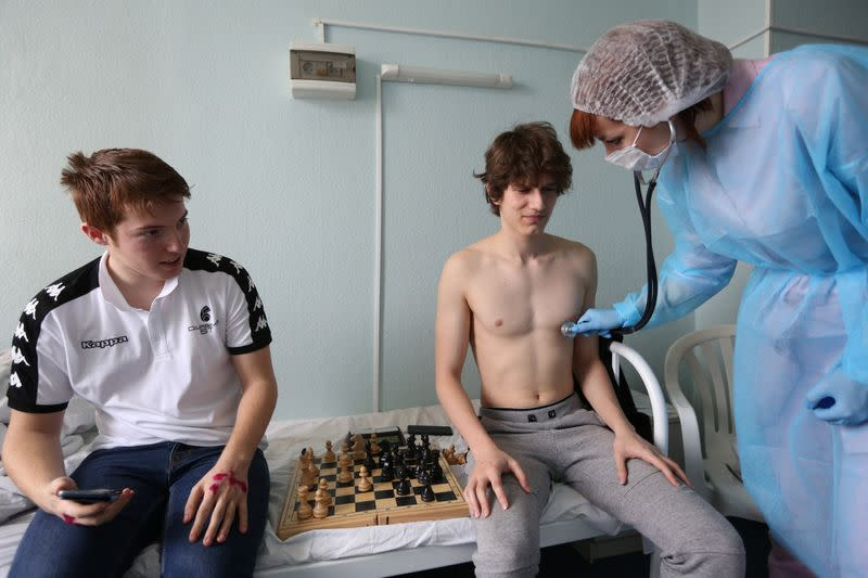 A nurse wearing protective gear checks the health of chess players from France at a hospital in Murmansk