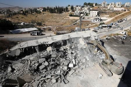 An Israeli military bulldozer demolishes a building near a military barrier in Sur Baher, a Palestinian village on the edge of East Jerusalem in an area that Israel captured and occupied in the 1967 Middle East War