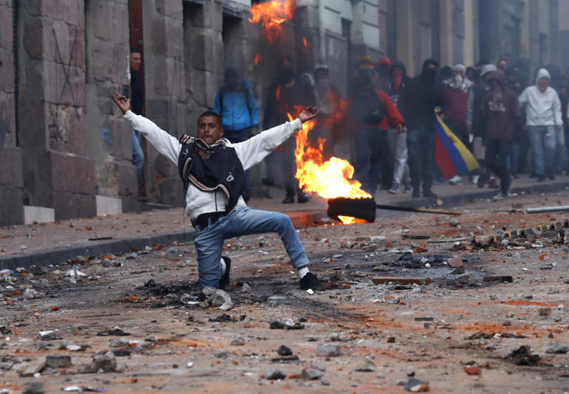 Protesters against the president stand off with police near the government palace during a transportation strike in Quito, Ecuador, Thursday, Oct. 3, 2019. Ecuador's president has declared a state of emergency to confront rowdy street protests and a nationwide transport strike over his decision to end government fuel subsidies and relax labor protections. (AP Photo/Dolores Ochoa)