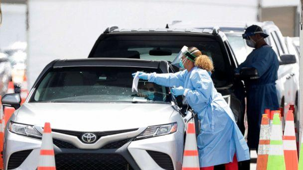 PHOTO: Healthcare workers prepare to test drivers at a drive-through coronavirus testing site outside of Hard Rock Stadium, June 26, 2020, in Miami Gardens, Fla. (Wilfredo Lee/AP)