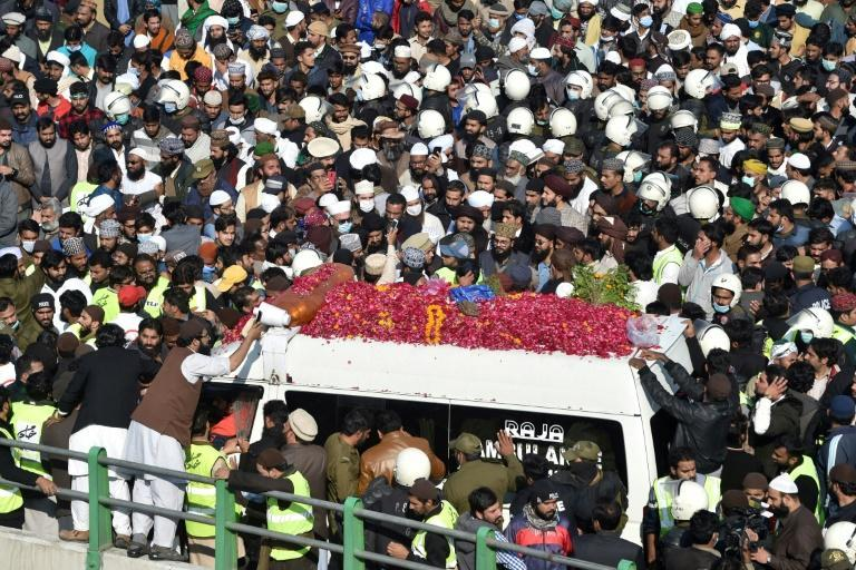 Mourners gather around an ambulance carrying the coffin of hardline Pakistani cleric Khadim Hussain Rizvi for the funeral procession in Lahore