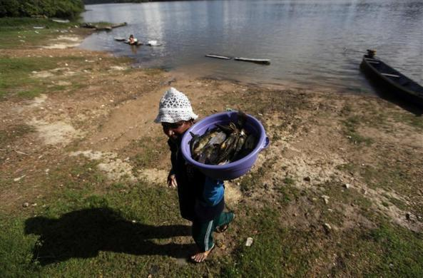 A man carries a bucket with fish from the Tapajos river in the village of Pimental in Itaituba, state of Para May 26, 2012.