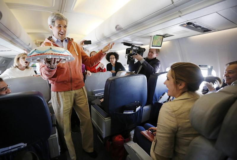 Secretary of State John Kerry presents a birthday cake to traveling CBS correspondent Margaret Brennan, right, on a from Kabul to Paris, Tuesday, March 26, 2013. Kerry went to Paris for talks with French officials about aid to the Syrian opposition and the situation in Mali. (AP Photo/Jason Reed, Pool)