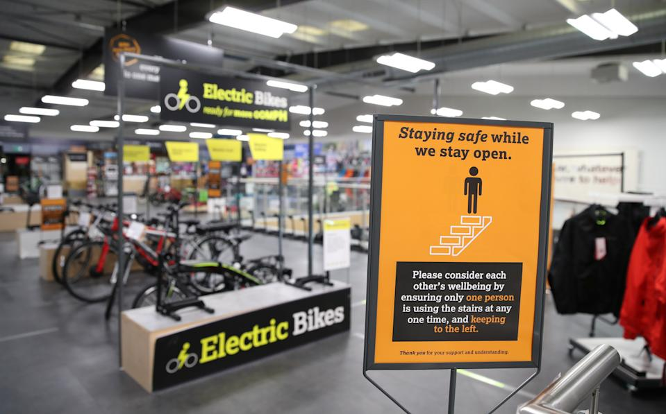 A social distancing sign is pictured in a Halfords store, after the government announced a new plan on walking and cycling projects, following the coronavirus disease (COVID-19) outbreak, in Luton, Britain July 28, 2020. REUTERS/Peter Cziborra