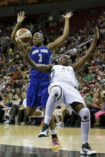 Seattle Storm's Nakia Sanford, right, tumbles backwards after being fouled by New York Liberty's Kelsey Bone in the first half of a WNBA basketball game Friday, June 28, 2013, in Seattle. (AP Photo/Elaine Thompson)